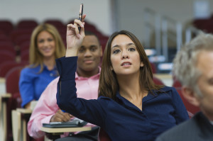 Female executive raising hand during a business lecture amid colleagues