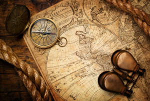old compass, binoculars and rope on vintage map